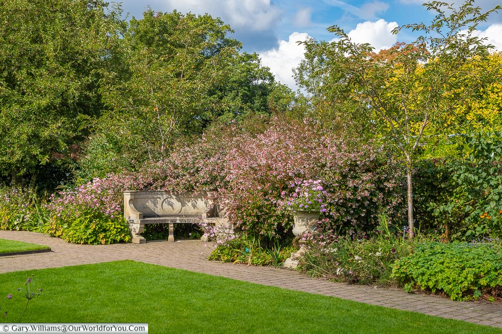 A stone, semi-circular, bench at the far end of the Cottage Garden in amongst the pink flowers of the border.