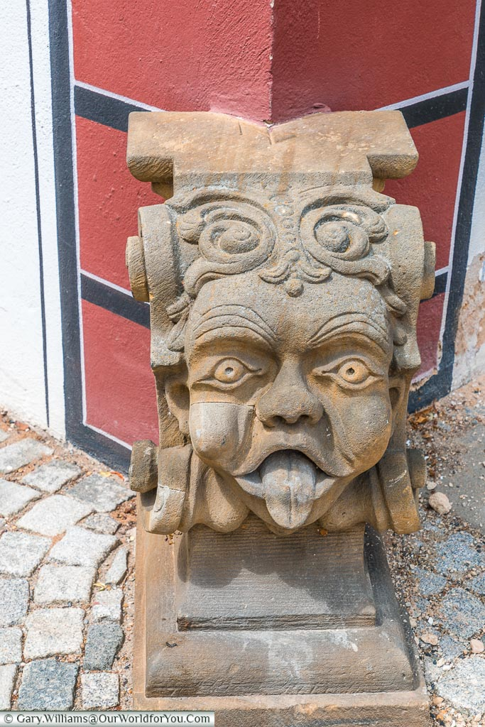 A stone decoration of a cheeky head with its tongue sticking out at the base of a house.
