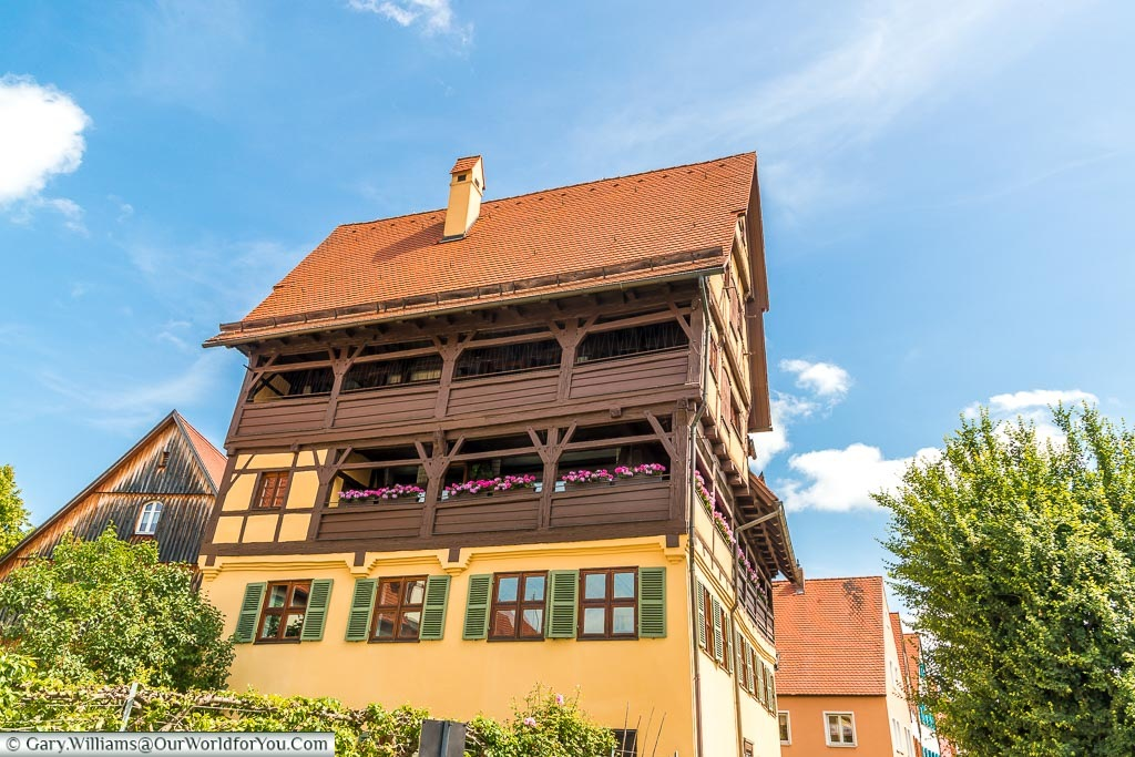 A traditional home with gabled upper decks with brightly coloured flower boxes on the middle row.