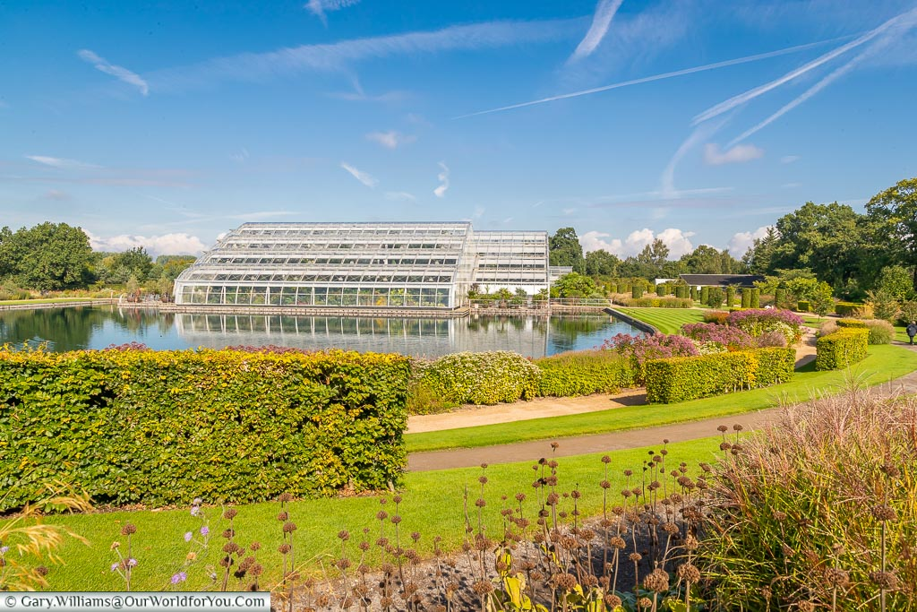 A view of the Glasshouse across the lake from the borders around it.