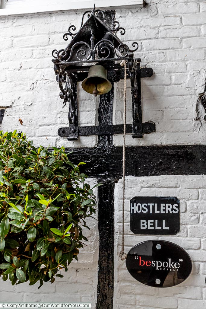 """A bell mechanism, with a rope handing down, labelled as the 'Hostlers Bell' above a sign for """"bespoke hotels""""."""
