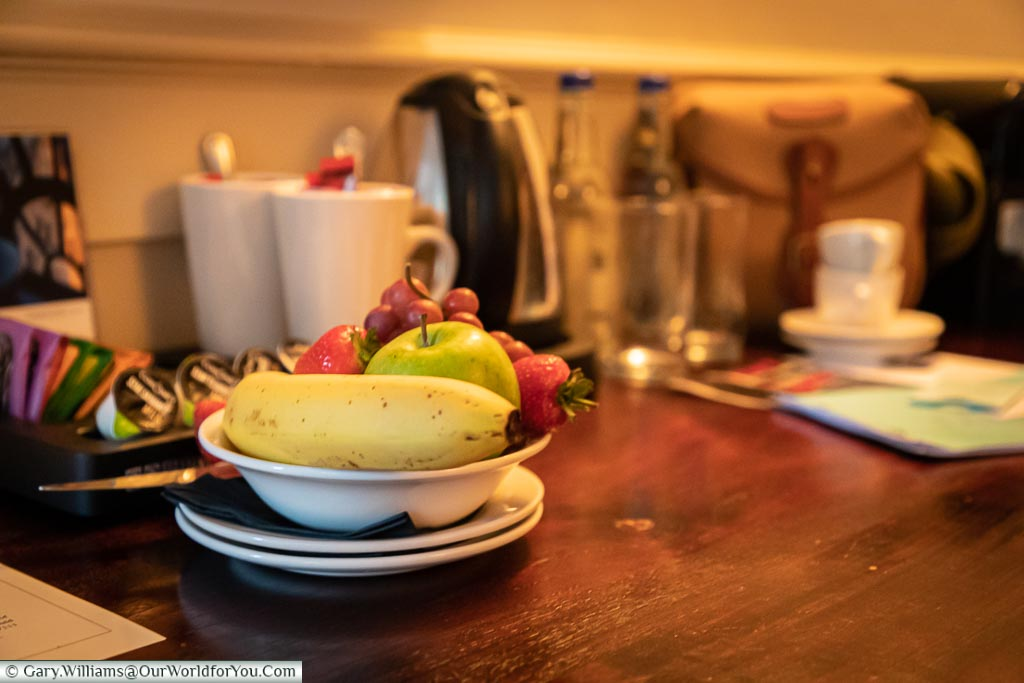 A bowl of fruit on the desk in the room that gives you ample space to work on should you need to.