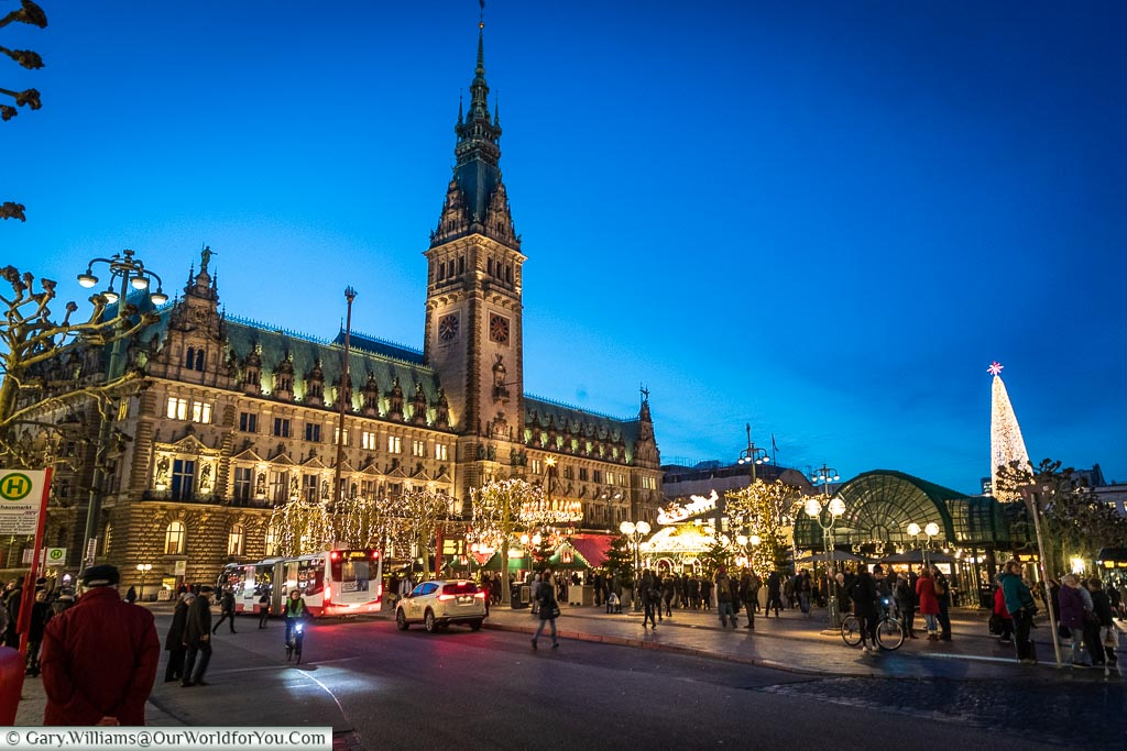 A view across the street to Hamburg's Rathaus, and its Christmas market, under the blue sky of dusk