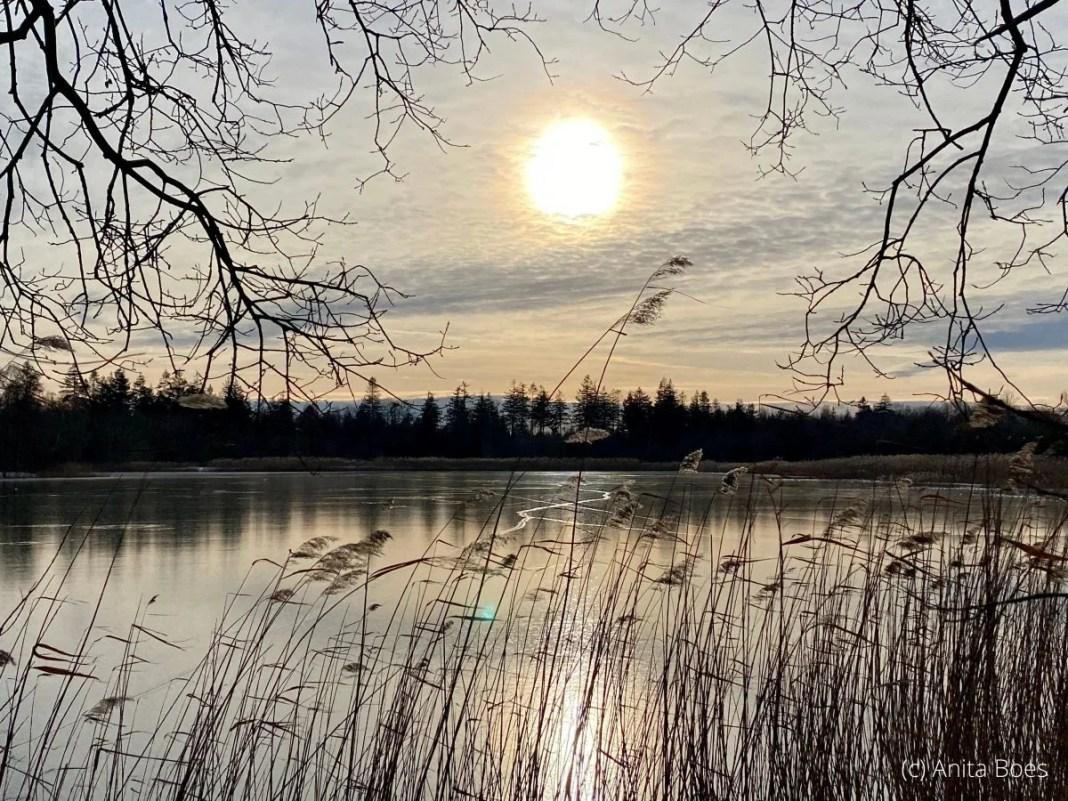 De zon zakt bij de Kuinderplas in Kuinderbos.