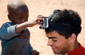 A boy of the Himba tribe (the last nomadic tribe of Namibia) plays with a team member's GoPro