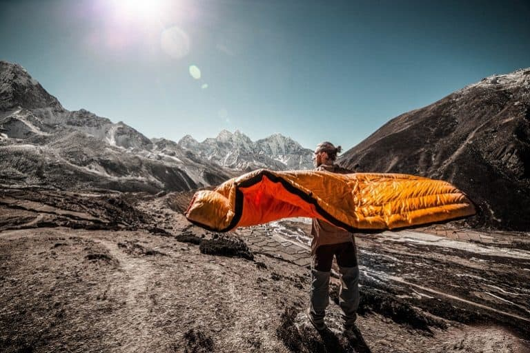 Mann mit Schlafsack vor Bergkulisse