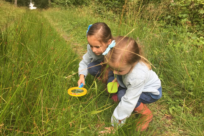 two girls peering into grass with magnifying glass