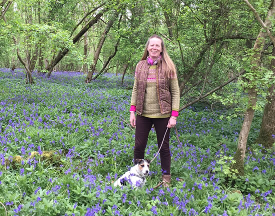 woman with dog standing in bluebells