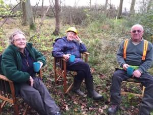 three people sitting in woodland drinking tea