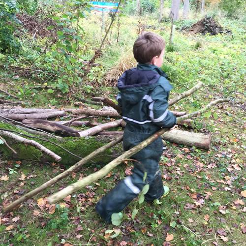 boy dragging logs