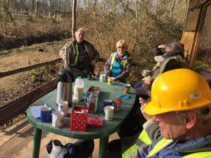 men and women sitting in wood enjoying a coffee break