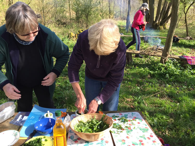 two women preparing food outdoors