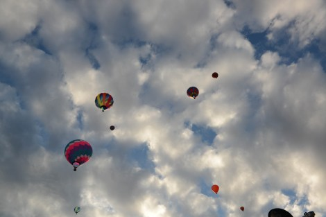 Fluffy Clouds and balloons flying at many heights.