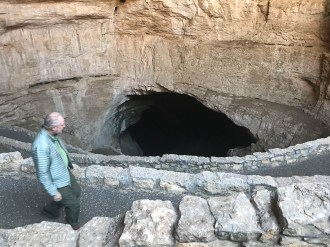 Bruce descends into the natural cave opening