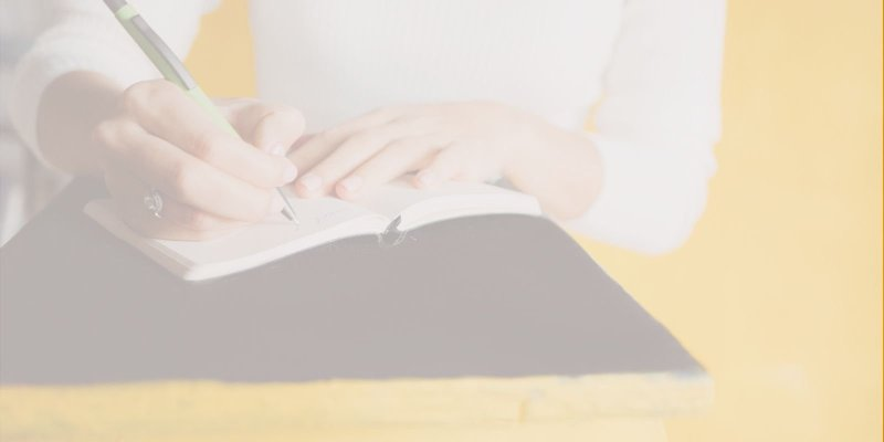 Woman thinking about what to blog about in her notebook