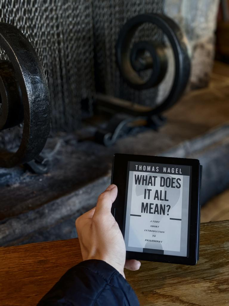 Man holding up an ebook called 'What does it all mean' to find the real you