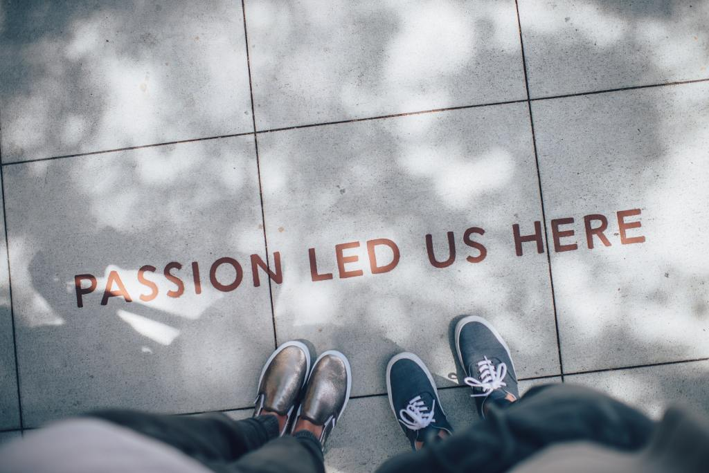 Two people looking down on the pavement reading the words passion lead us here (symbolic of finding your passion career)