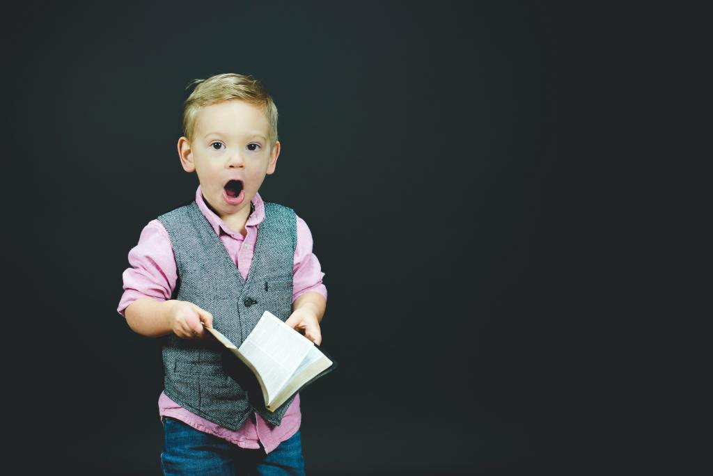 A little kid with his math open in astonishment as he holds a book in his hand to get a change of perspective