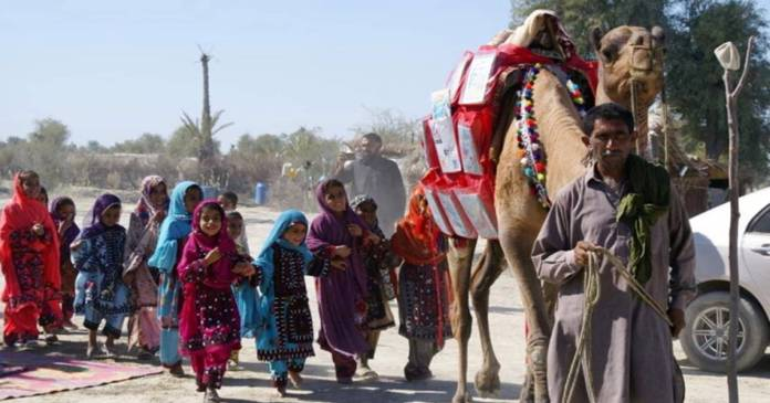 Children react as Roshan the camel carries books in Mand