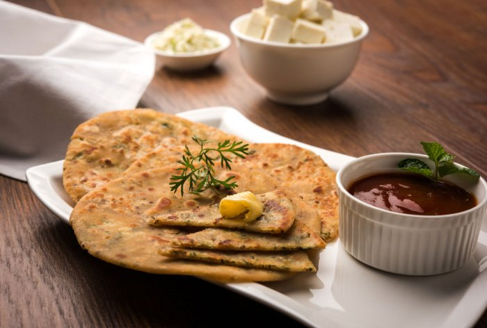 Stuffed Paneer Paratha with melting butter, served with fresh Cottage Cheese cubes and tomato ketchup