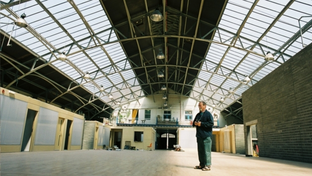 Former Out of the Blue Arts & Education Trust Chairperson John Molleson inspects the new flooring installed into the Drill Hall.
