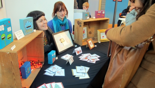 Customers and stallholders chat at an Out of the Blue Arts Market, where framed pictures and postcards are on sale.