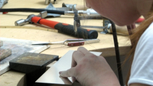 Precious Metals crafting, a silversmith using fine tools to create jewellery.