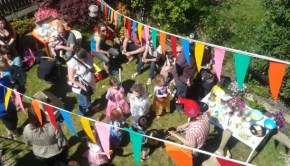 A birdseye view of a happy cowd of adults and children at a Happy Ears event in a park on a sunny day.
