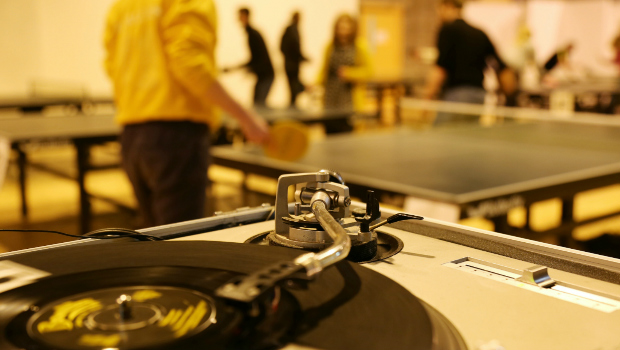 Table tennis players compete in background at a Wiff Waff Wednesday event while a vinyl record spins in the foreground.