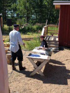 Pikku-Pekka haaveilee tukkimiehen töistä. Vanhempi mies keskustelee kuvassa Pekan kanssa.