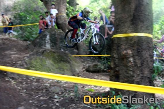 A downhill racer jumps a drop