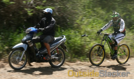 Downhill bike being towed by a motorcycle to the top of the antenna hill