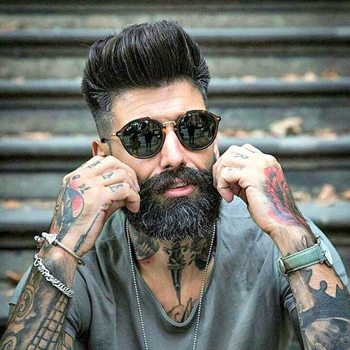 Man with black glasses and fade with modern pompadour and beard