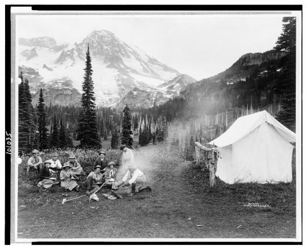 Camping party of men and women cooking at campfire and eating near tent in Indian Henry, Mt. Rainier National Park, Washington