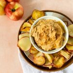 A bowl with pumpkin dip served with apple chips on the side with a pink background