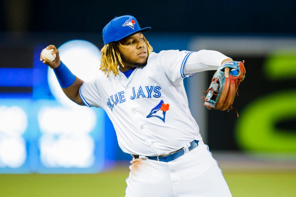 Vladimir Guerrero Jr. in white Blue Jays jersey throwing the baseball.