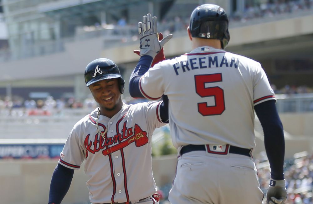 Freeman high fiving his teammate on rout to the Brave's challange the NL mountain