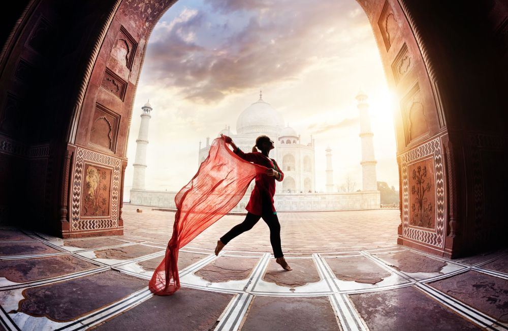 Woman with red scarf dancing near Taj Mahal in Agra, Uttar Pradesh, India