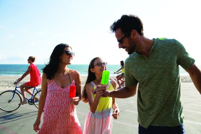 A family wearing glasses and sunglasses enjoy popsicles near a sunny beach.