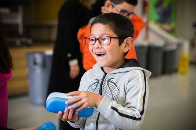 A young boy smiles while wearing a new pair of glasses and holding a blue glasses case.