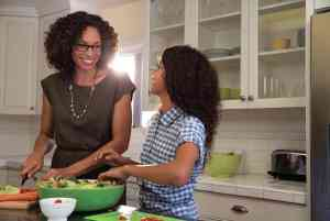 A mother and her young daughter smile at each other while wearing glasses and preparing a salad in their kitchen.