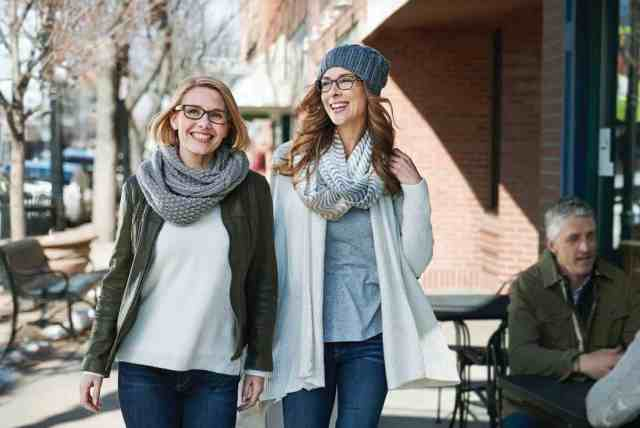 Two satisfied Pearle Vision customers walk down the street while wearing glasses on a winter day.