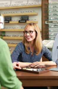 A customer smiles while trying on a pair of glasses in a Pearle Vision EyeCare Center. A store associate is also pictured out-of-focus in the foreground.
