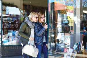 Two women in glasses happily window-shop.