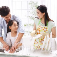 Family washing dishes in kitchen