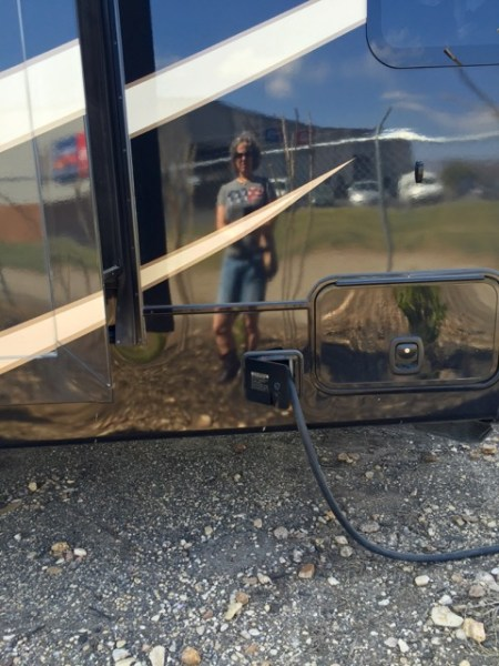 Not just my reflection in an RV, but a lesson. If you visit an RV dealership on your way to the RV show, and happen to mention that's where you're headed, the sales dude just might hand you a couple of complimentary tickets. That little excursion saved us 12 bucks!