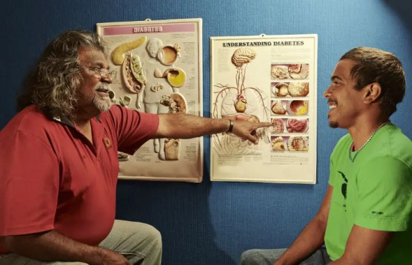 Here, Geraldton Aboriginal Health worker, Eric Dalgety, speaks with a young client, Kane. Photo: Jason Malouin/Oxfam AUS.