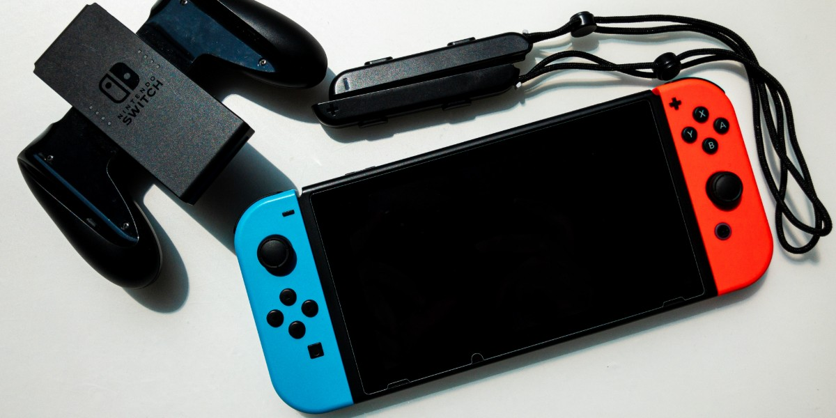 A Nintendo Switch console with wrist-straps and a Joy-Con grip