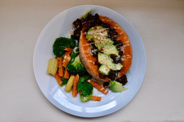Baked sweet potato topped with beans and other vegetables