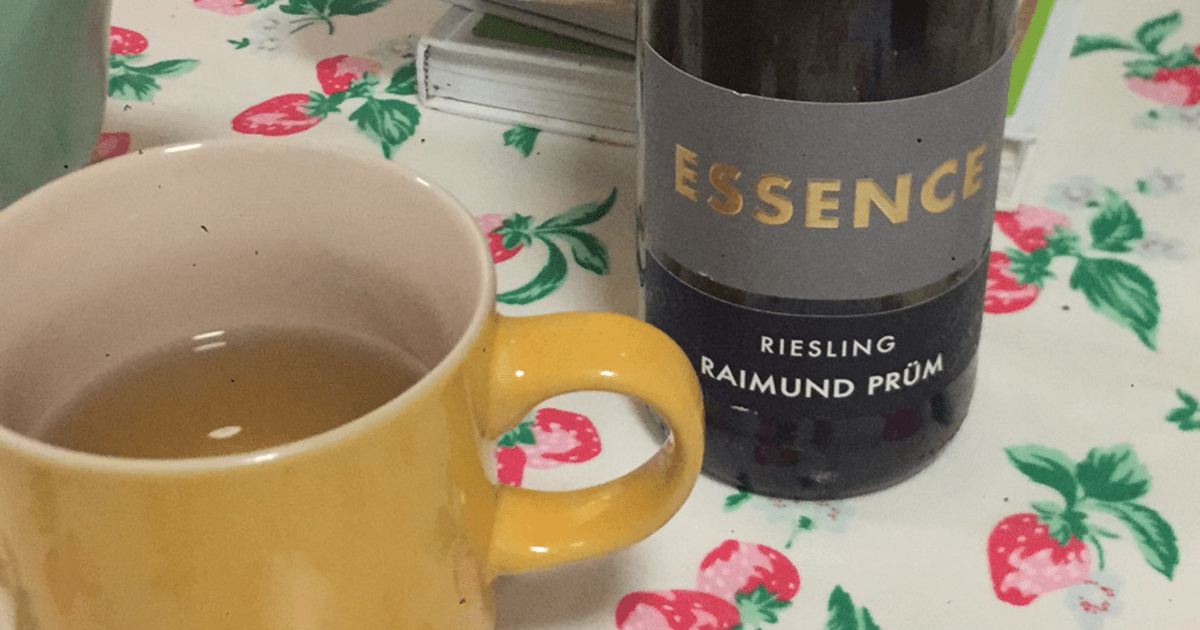 A bottle of white wine called 'Essence: Riesling Raimund Prüm' on a table with a yellow mug.